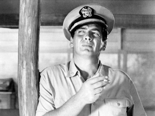 American actor Victor Mature wearing a navy uniform and smoking a cigarette in the film The Sharkfighters.