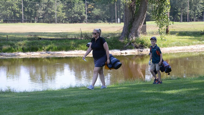 Sarah O'Shea and her 9-year-old son Michael O'Shea walk along a pond at Maple Grove Golf Course.