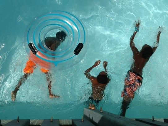 Three boys float the lazy river at Sun Splash Family