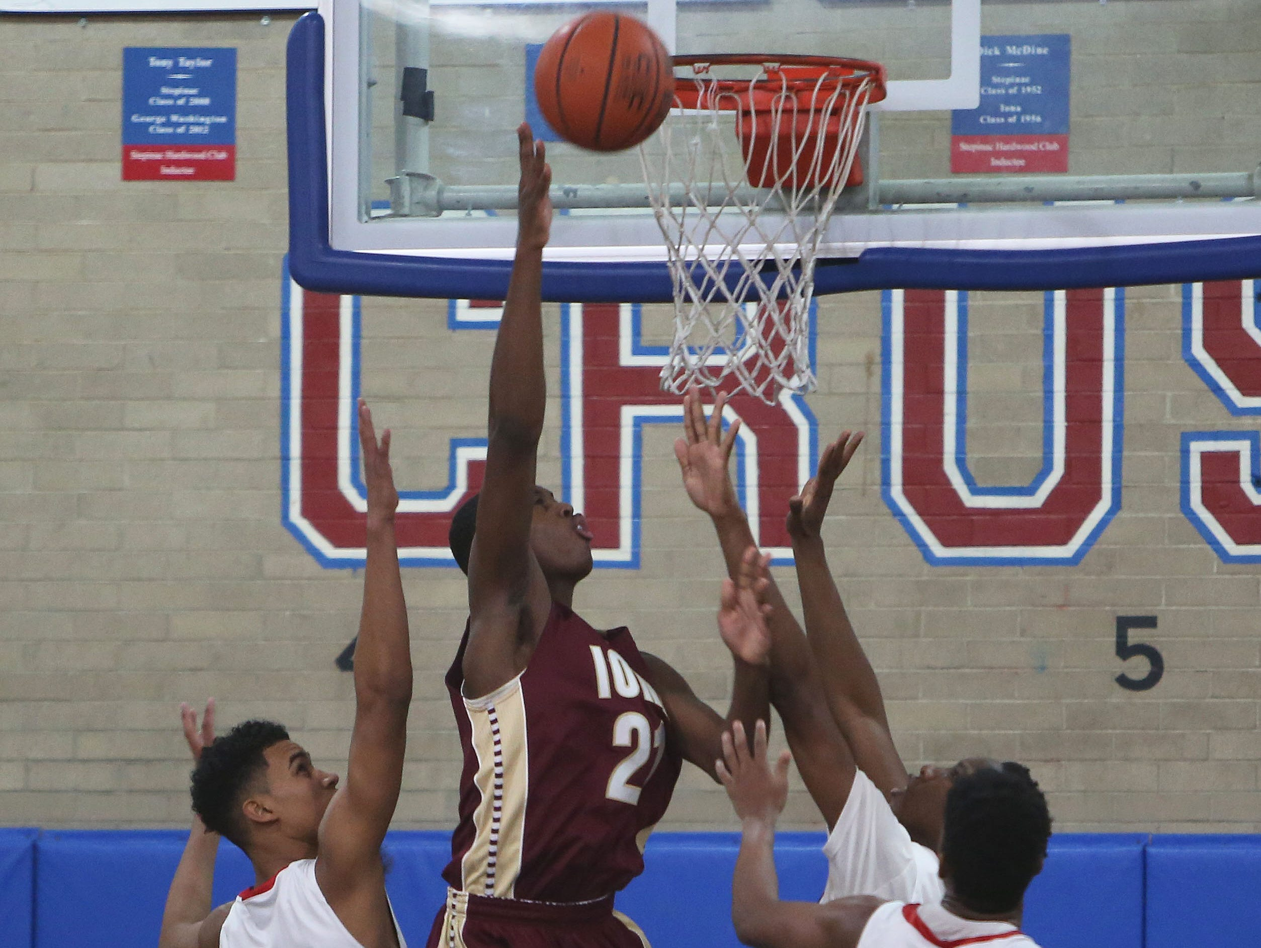 Iona's Josh Alexander (21) tries to go up for a shot in front of Stepinac's Jordan Tucker (5) and Jorden Means (0) during boys basketball action at Archbishop Stepinac High School in White Plains Jan. 8, 2016.