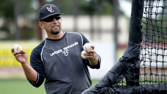 """UL assistant coach Matt Deggs throws to players during batting practice at M.L. """"Tigue"""" Moore Field."""