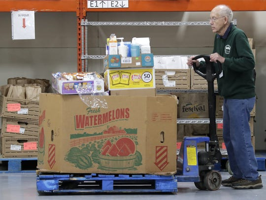 Volunteer Robert Vollmer moves a pallet of donations last week at the St. Joseph Food Program in Menasha. Wm. Glasheen/USA TODAY NETWORK-Wisconsin.