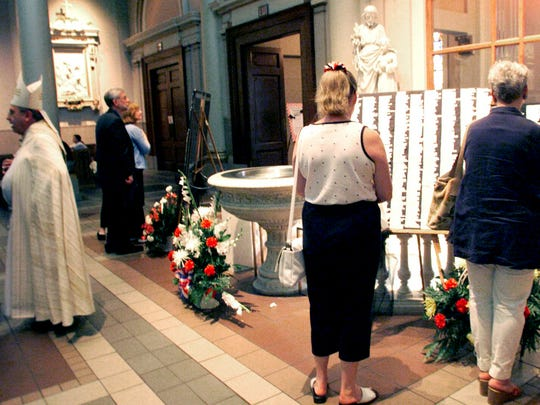 Most Reverend Edward U. Kmiec, left, Bishop of Nashville, speaks with people as participators in the September 11 service at the Cathedral of the Incarnation look at the lists of names of all of the victims from last year's tragedies Sept. 11, 2002.