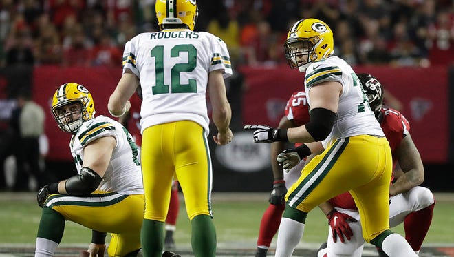 Green Bay Packers guard T.J. Lang (70) and center Corey Linsley (63) look to quarterback Aaron Rodgers (12) for instructions against the Atlanta Falcons at the Georgia Dome in Atlanta, Georgia Sunday, January 22, 2017.