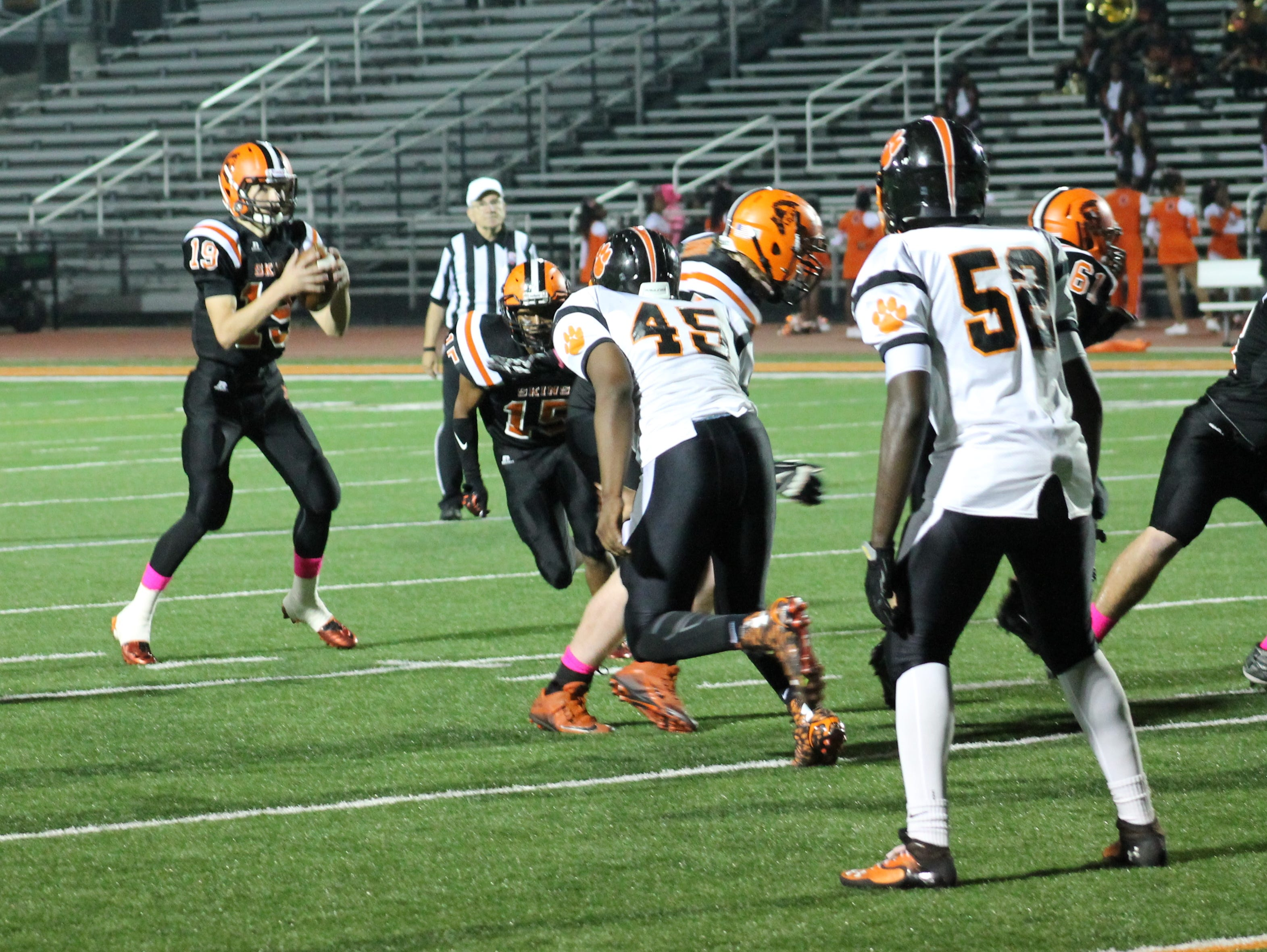 Anderson sophomore quarterback Jay Volpenhein (19) takes the shotgun snap before running for a Redskins score against Withrow.