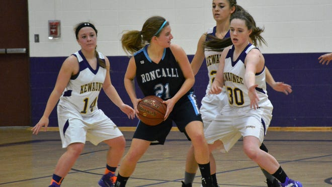 Kewaunee's Angie Kudick, Abby VanGoethem and Ellie Olsen work on blocking Roncalli's Jamie Hoban during the Storm home opener Nov. 18.
