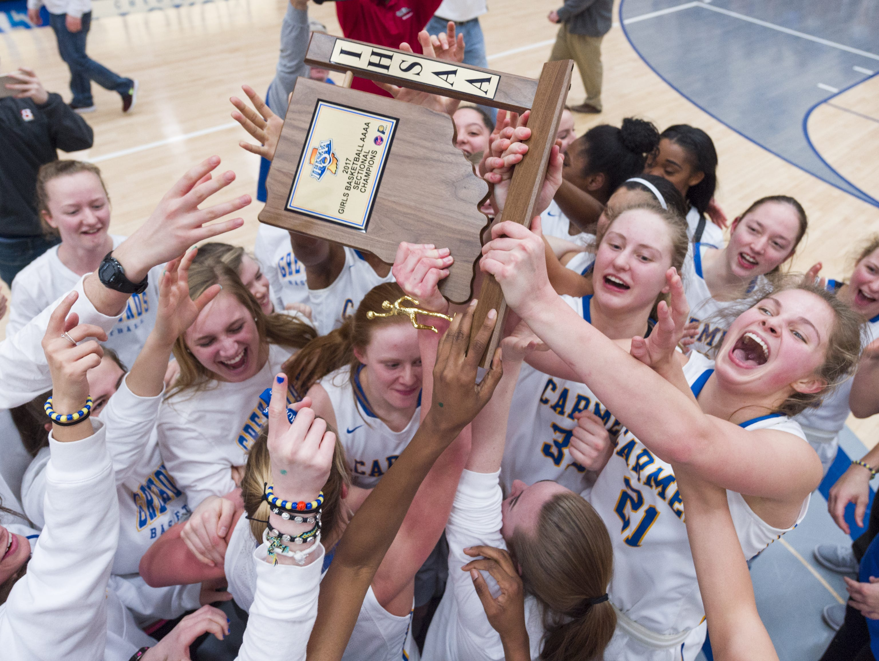 Carmel High School players celebrate with their trophy after winning the 2017 IHSAA Girl's Basketball Sectional Tournament championship game at Hamilton Southeastern High School Saturday, Feb. 4, 2017. Carmel won 62-57.