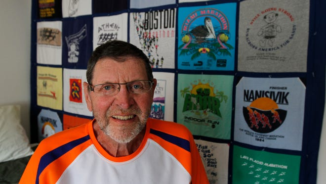 Norm Frank in his room at Legacy at Clover Blossom in Brighton in 2010. Behind Frank is a large quilt made up of T-shirts Frank received from the hundreds of marathons he has run in. Frank, who died on Tuesday, completed 965 marathons.