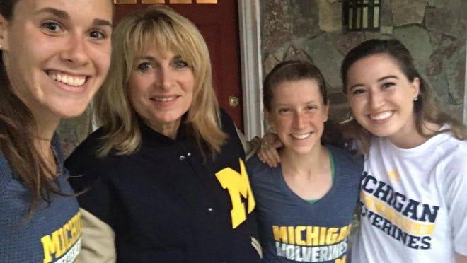 Melanie Weaver Barnett, class of '83, receives her jacket from UM athletes Jamie Morrissey, left, Erin Finn and Haley Meier.