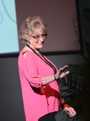 Dana Dayton, a 12-year breast cancer survivor, waves as she models an ensemble from Sassy Girl at the 2015 Threads fashion show held Sunday at the Coughlin-Sauders Performing Arts Center. This was Dayton's first time participating in the show.