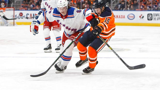 New York Rangers' Jacob Trouba (8) and Edmonton Oilers' Josh Archibald (15) battle for the puck during second period NHL hockey action in Edmonton, Alberta, Tuesday, Dec. 31, 2019.