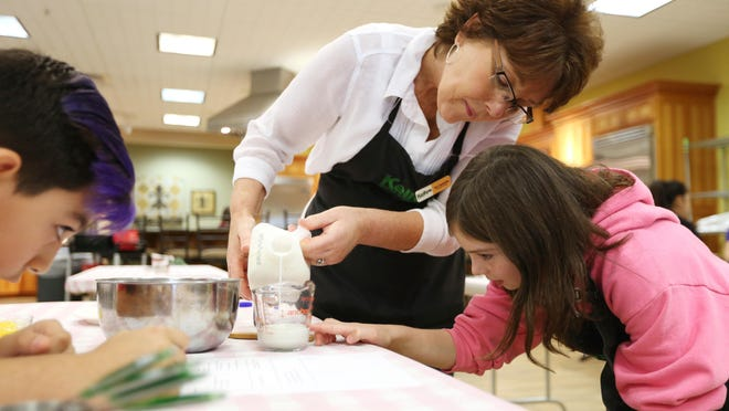 Instructor Tori DeWolfe helps Mahaylah Richardson, 8, measure milk during a cooking class at Kelly's Home Center in Salem. Participants learned how to make Creme Brulee muffins, mini corndog muffins and chocolate peanut butter chip muffins.