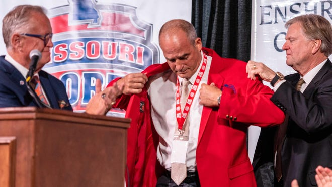 Former Missouri head football coach Gary Pinkel, center, puts on his Missouri Legends jacket before giving a speech last year for being enshrined into the Missouri Sports Hall of Fame as a Missouri Legend. Pinkel is now on the ballot for the College Football Hall of Fame.