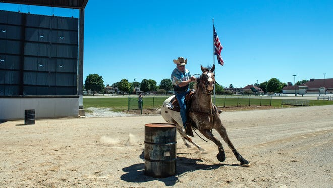 Ron Harkins, of Felton, races around a barrel during the qualifying round at the first day of the Wild West Summer Fest, Saturday, July 7, 2018. The event showcases horse barrel racing, harness racing, horsemanship events and food and games.