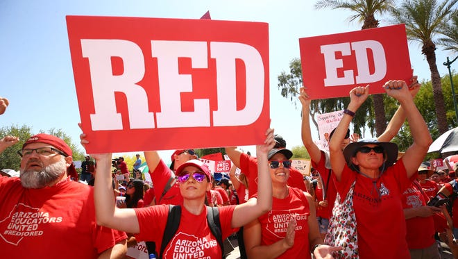 Angela Murphy (center) joins fellow Arizona teachers during a rally at the Arizona state Capitol for higher pay and more education funding on April 27, 2018, in Phoenix.