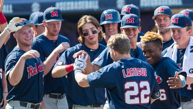 Ole Miss catcher Henri Lartigue (22) celebrates with teammates last week. Ole Miss will face the toughest regional this weekend, D1Baseball's Kendall Rogers said.