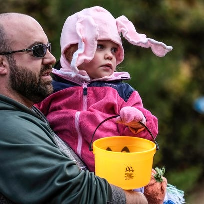 Marni LaPaugh, gives her son Hayden, 3, a ride on her back as they look at the lions and tigers during Boo at the Zoo at Potter Park Zoo on Saturday.