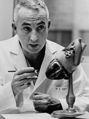 In this undated photo provided by Stanford University of Dr. Norman Shumway shows him with a model of a human heart similar to the one transplanted in a four-hour operation at Stanford School of Medicine on Jan. 6, 1967. Shumway was the first surgeon to perform a heart transplant operation in the United States and a leading pioneer in the field, died Friday, Feb. 10, 2006, of lung cancer, according to a spokeswoman at Stanford University. He was 83.. (AP Photo/Stanford University, ho)