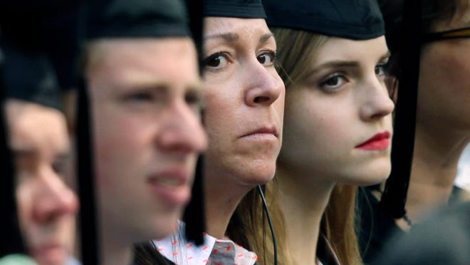 In this Sunday, May 25, 2014 photo, actress Emma Watson, right, sits beside a woman, left, later seen wearing a badge and with a handgun visible at her side, during commencement services at Brown University in Providence, R.I.  A Brown spokesman said Tuesday, May 27, 2014, he was unable to answer questions about why the British actress had the undercover armed guard sitting with her during graduation ceremonies. (AP Photo/Steven Senne) ORG XMIT: BX102