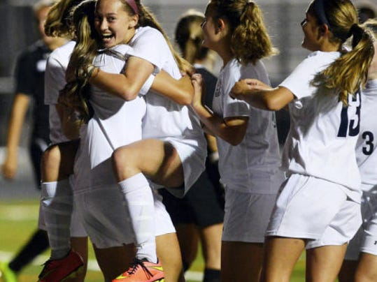 Dallastown's Paige Hartman celebrates with teammates following a 2014 win over Central York.