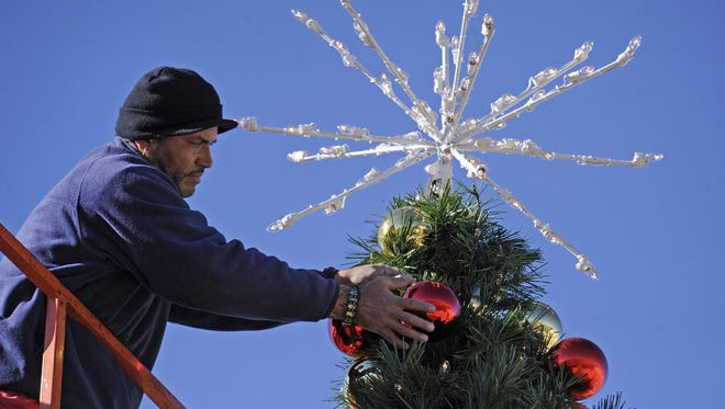 Jose Rodriguez hangs decorations on the Christmas tree at the Summit shopping center in Reno on Wednesday, Nov. 16, 2011.