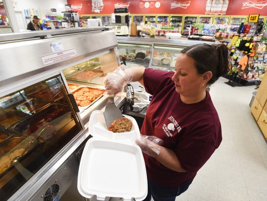 Andrea Elliott prepares a to-go meat loaf meal at Hunters Run at the intersection of Ohio routes 37 and 13 at Six Mile Turn.