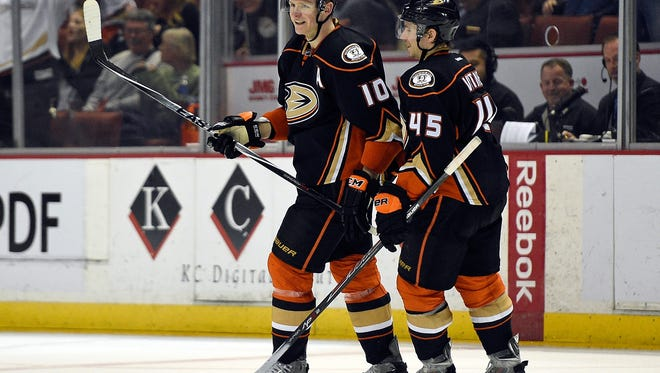 Corey Perry, left, celebrates with defenseman Sami Vatanen after scoring a goal for a hat trick.