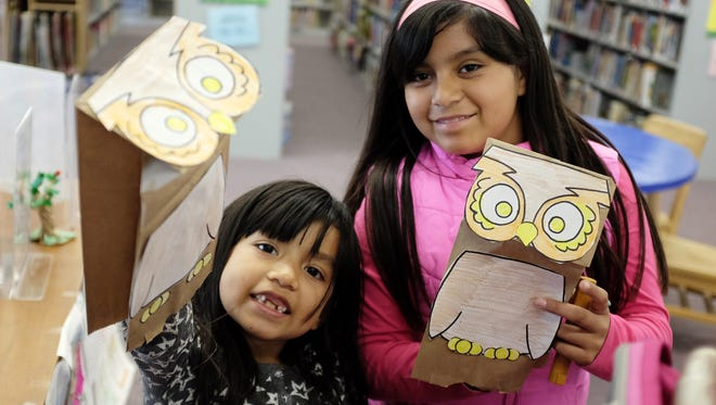 Guadalupe Loredo, 6, and her sister Diane, 10, show off the owl puppets they made at the Steinbeck Library during Tuesday's birthday celebration for author Beverly Cleary, 100 years old on April 12th.