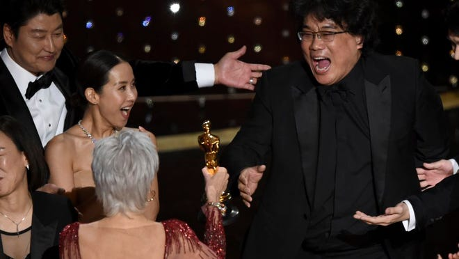 "Bong Joon Ho, right, reacts as he is presented with the award for best picture for ""Parasite"" from presenter Jane Fonda at the Oscars on Sunday."