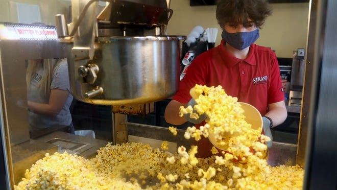 Noah McCloskey, 16, fills a large order of popcorn for a customer May 29 at the Strand Theatre, 28 E. Winter St. in downtown Delaware. The theater is offering curbside sales of popcorn and drinks from 4 to 6 p.m. Fridays and Saturdays as part of a fundraising effort to reopen the establishment, once permitted, after shutting down in response to state mandates during the COVID-19 coronavirus pandemic.
