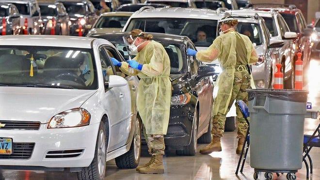 North Dakota National Guard soldiers Spc. Samantha Crabbe, left, and Master Sgt. Melanie Vincent administer COVID-19 tests, Tuesday, Nov. 17, 2020, inside the Bismarck Events Center in Bismarck, N.D.