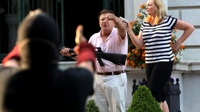 Armed homeowners Mark and Patricia McCloskey, standing in front their house along Portland Place confront protesters marching to St. Louis Mayor Lyda Krewson's house in the Central West End of St. Louis in late June.