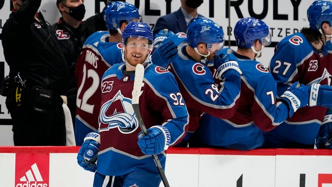 Colorado Avalanche left wing Gabriel Landeskog, front, smiles after he was congratulated as he passed the team box after scoring his second goal in the second period of an NHL hockey game against the St. Louis Blues, Friday, Jan. 15, 2021, in Denver.