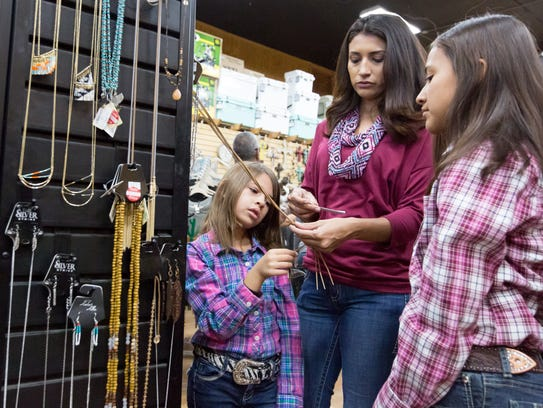 Sofia Luchini and her daughters Claire, 6, left, and Vanessa, 10, look over the jewelry on sale Saturday, November 25, 2017, during Small Business Saturday at Horse & Hound Feed N Supply.