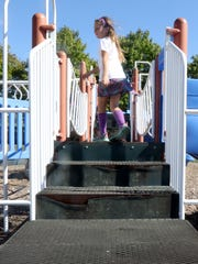 Kids play on damaged playground equipment at Iola Scandinavia Middle School.
