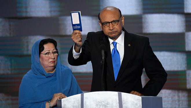Khizr Khan, father of fallen U.S. soldier Humayun S.M. Khan, offers a copy of The Constitution to Donald Trump as he speaks during the 2016 Democratic National Convention
