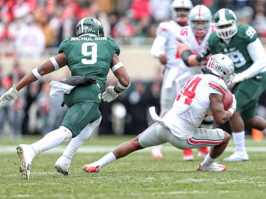 Ohio State receiver K.J. Hill catches a pass in front of Michigan State safety Montae Nicholson.