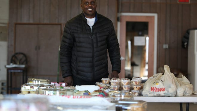 Bishop Billy Lane stands in front of some of the food donated by Wawa, B.J.'s Wholesale and Acme to his organization, Christian Growth Ministries.