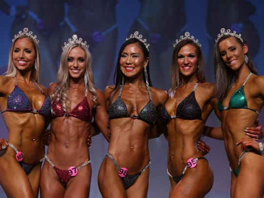 Julia Song, center, swept with her wins - taking first place in the Bikini Masters, Open and Overall categories at the 2017 NPC Washington IronMan Natural Bodybuilding, Classic Physique, Fitness, Figure, Bikini and Physique Championships in Seattle, Washington.