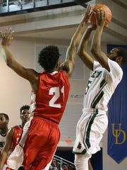 Mount Pleasant senior Rob Myrick's jumper is contested by Smyrna senior Ja'vier Worthy.