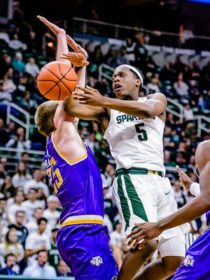 Cassius Winston ,5, of MSU dishes a pass around Mason Ramsey of Tennessee Tech to teammate Kenny Goins late in the 2nd half of their game Saturday December 10, 2016 in East Lansing.  Goins would slam the ball home for 2 points.