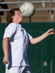 Rider's Kaleb Koetter heads the ball in the game against
