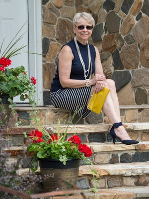 Judy Diogo Schrock wears a sleeveless, high-collar navy blue sweater with white-striped navy fitted skirt and ankle-strap heels by Liz Claiborne,