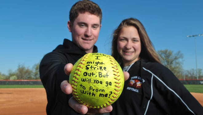 Julian Aguirre asked girlfriend, Beth DiChiara, to go with him to their prom by throwing her a softball between innings at her game at Fern Creek High School in Louisville, Ky.