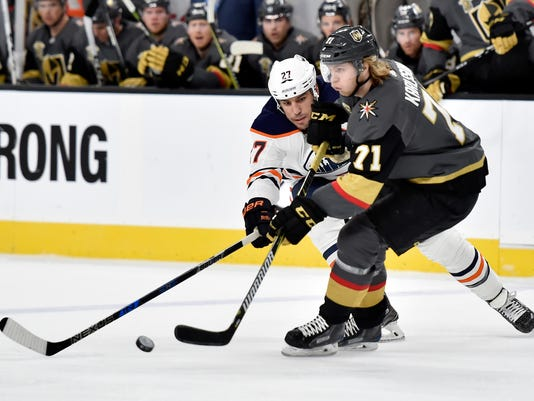 Edmonton Oilers left wing Milan Lucic (27) and Vegas Golden Knights center William Karlsson vie for the puck during the first period of an NHL hockey game Thursday, Feb. 15, 2018, in Las Vegas. (AP Photo/David Becker)