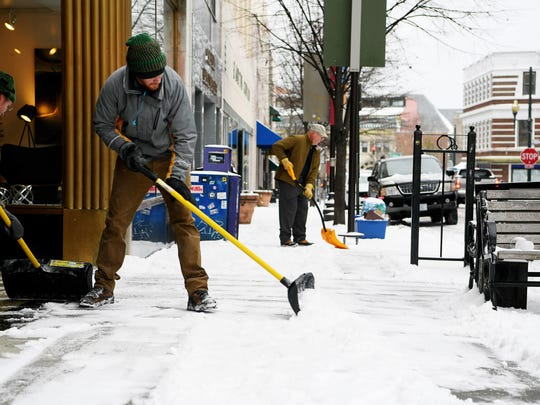 From left, Pete Wilson, Jeff Sheehan and Larry Holt shovel the sidewalk on Haywood Street in downtown Asheville January 17, 2018.