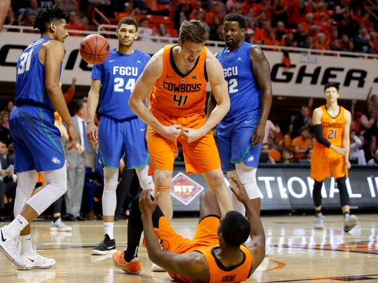 Oklahoma State's Mitchell Solomon (41) celebrates with teammate Tavarius Shine (5) in front of Florida Gulf Coast's Dinero Mercurius (31), Michael Gilmore (24) and Antravious Simmons (32) during an NCAA college basketball first-round NIT tournament game, Tuesday, March 13, 2018, in Stillwater, Okla. (Bryan Terry/The Oklahoman via AP)