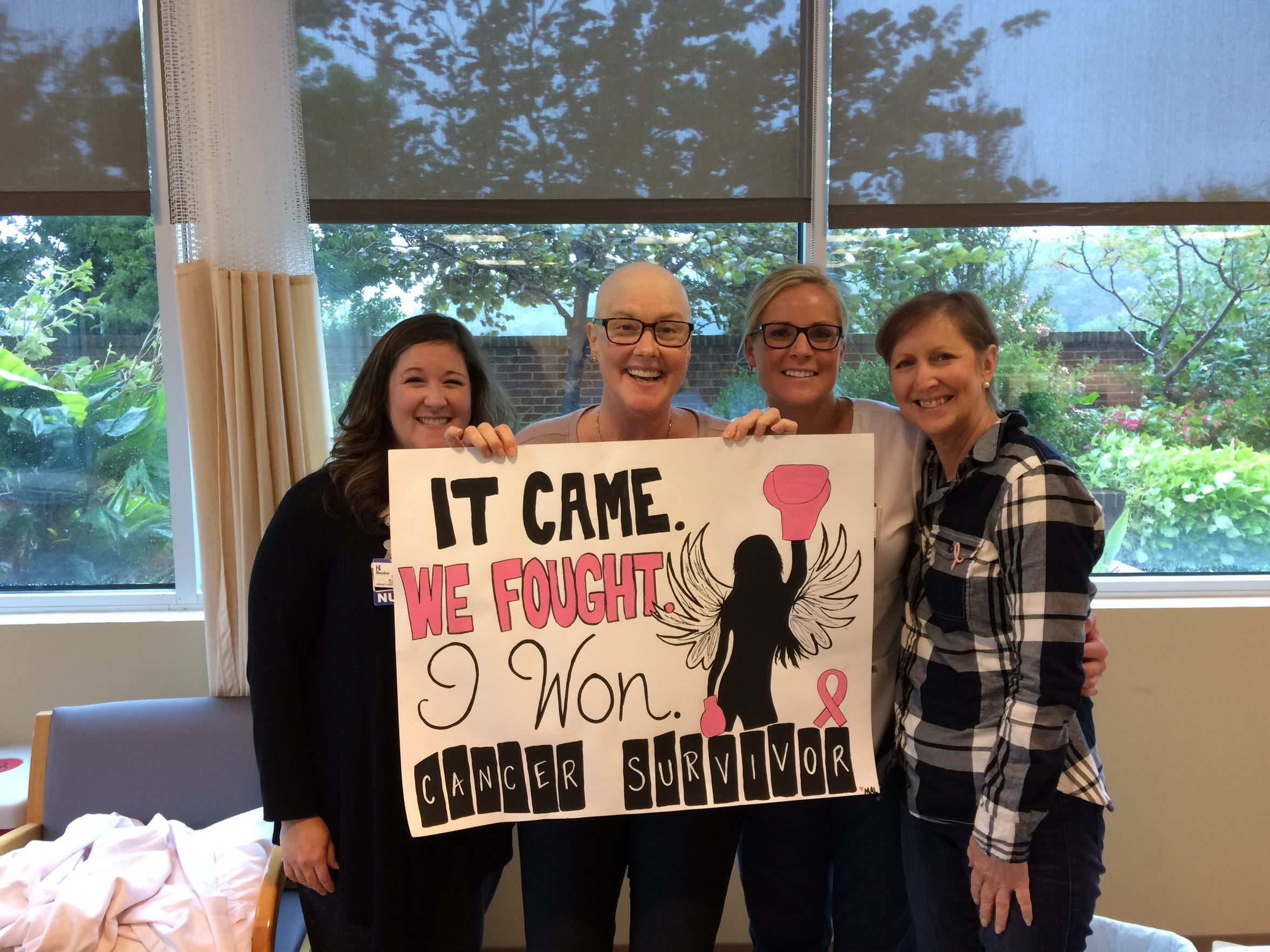 Lisa Welling poses for a photo on her final chemo session for breast cancer.