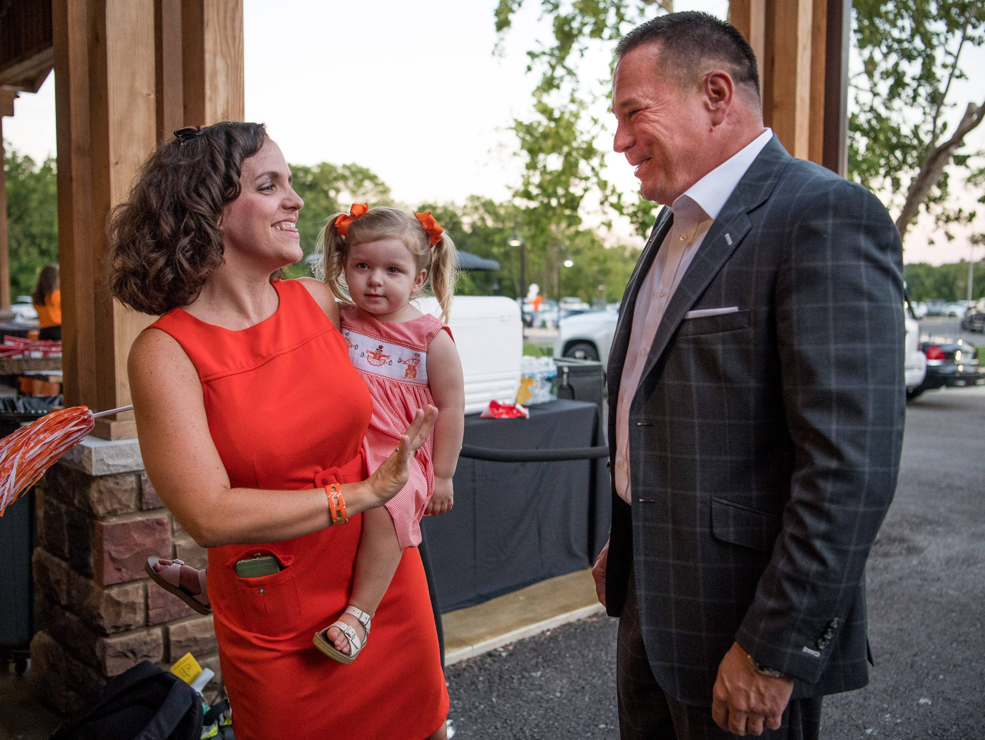 Butch Jones, University of Tennessee football coach, greets Lisa Debusk and her 2-year-old daughter Kate during a Big Orange Caravan event at The Barn at Sycamore Farms in Arrington, Tenn., Monday, July 10, 2017.