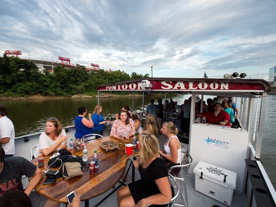 Guests enjoy drinks on the Pontoon Saloon on the Cumberland River in Nashville, Tenn., Friday, July 14, 2017.